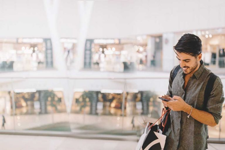 man texting on phone in shopping mall