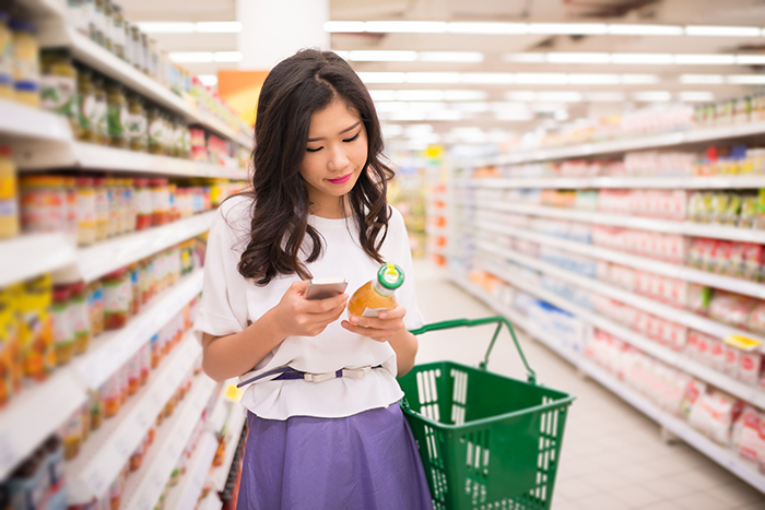 consumer checking product information on phone in store