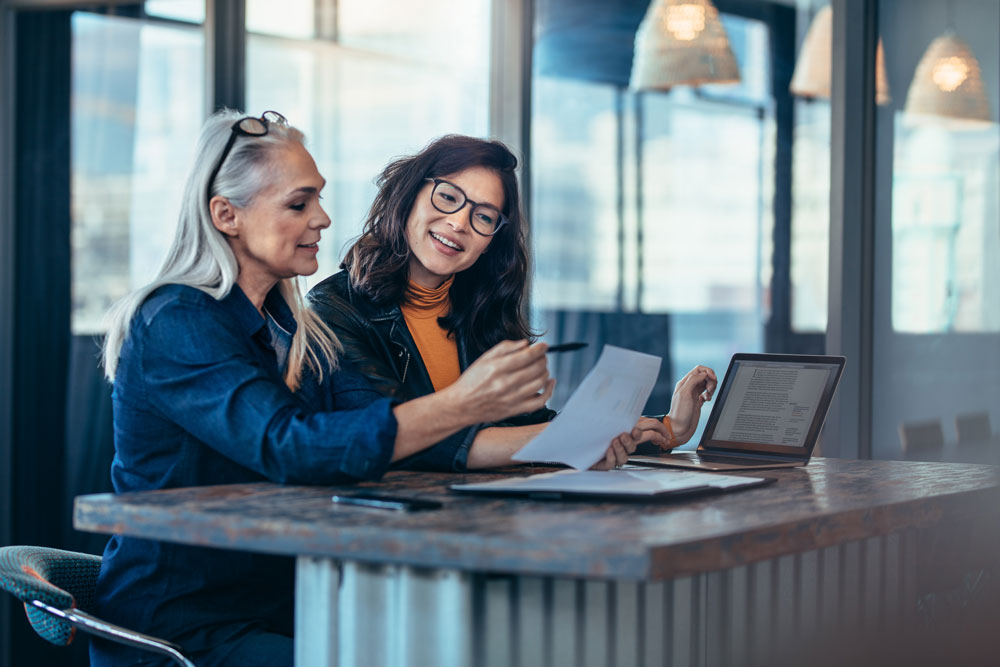 two women working in an office planning customer experience initiatives using knowledge management systems