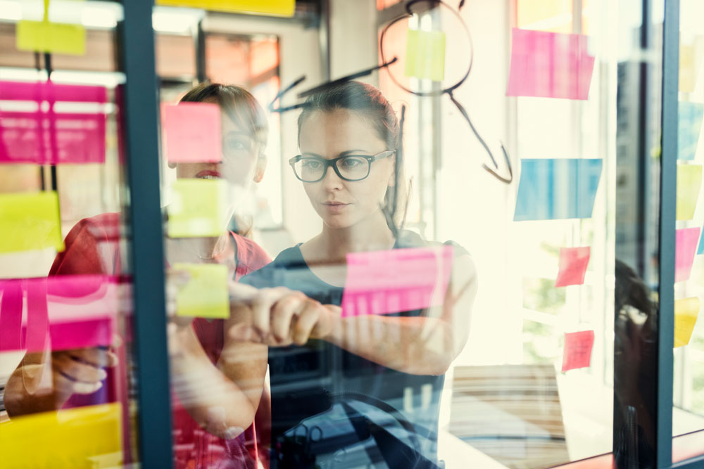woman in an office analyzing sticky notes