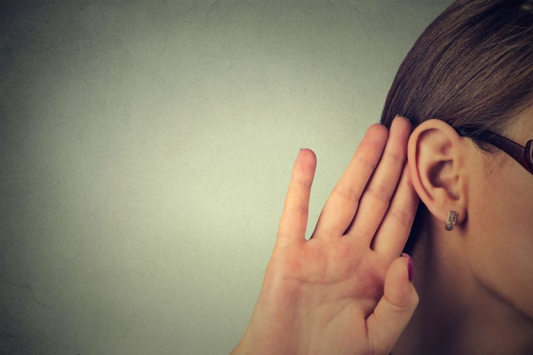 woman with hand behind ear listening to voice of customer