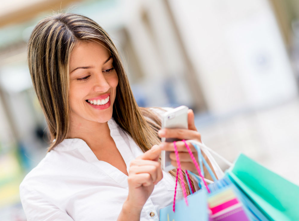 woman checking social media on her phone while shopping