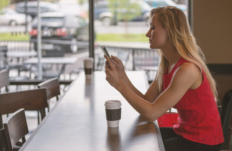 young woman using a phone at a table
