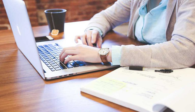 woman working at desk with tea