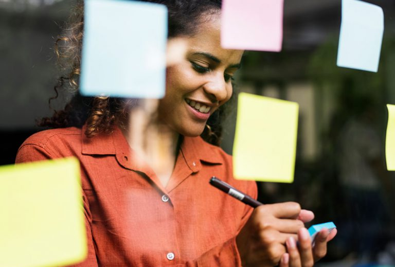 professional woman writing on sticky notes to assess cx benchmarks