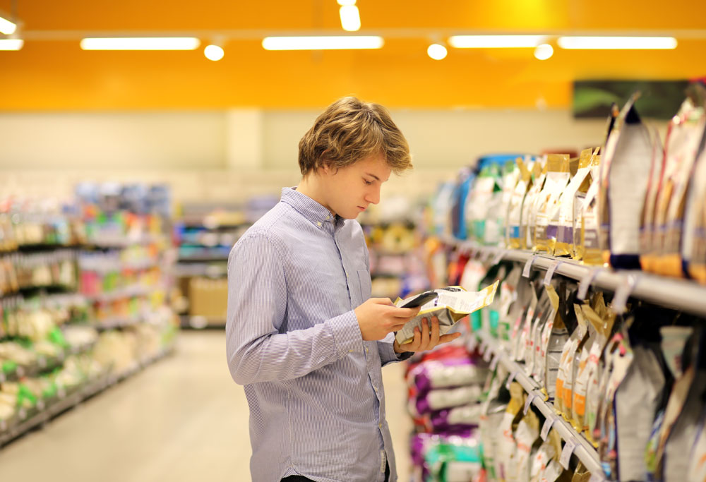 young consumer looking at phone standing in grocery store