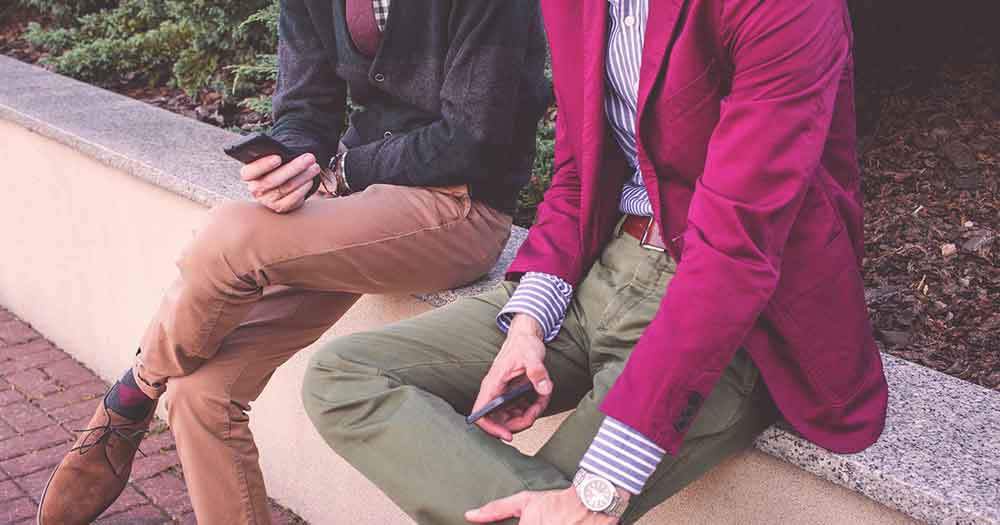 men in jackets using smartphones to engage in conversational commerce
