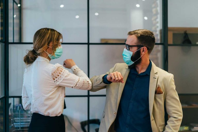 coworkers in office working distantly with masks
