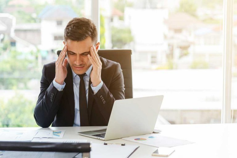 businessman working at laptop frustrated by free social listening tools