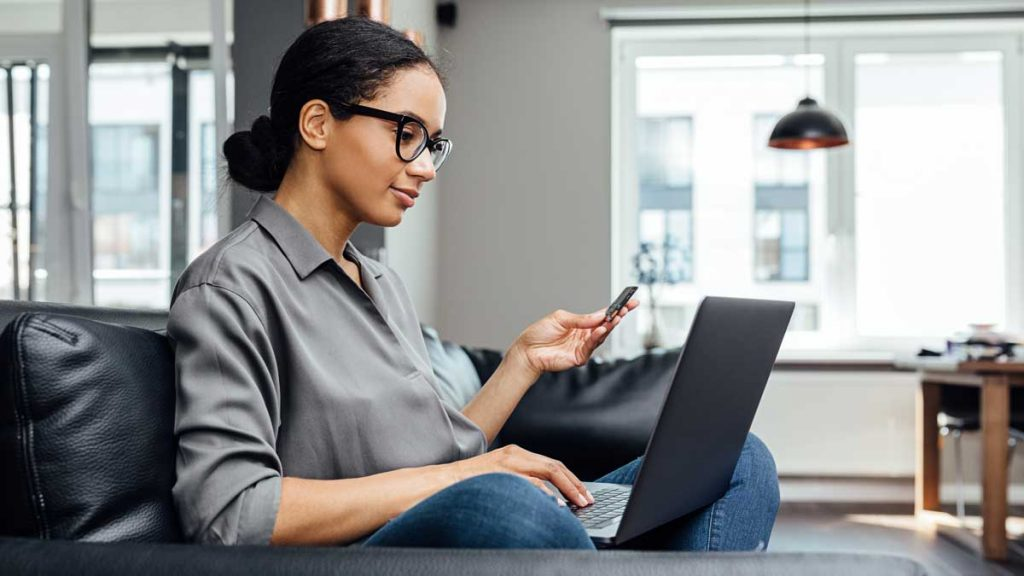 Woman online shopping on laptop while sitting on a couch.